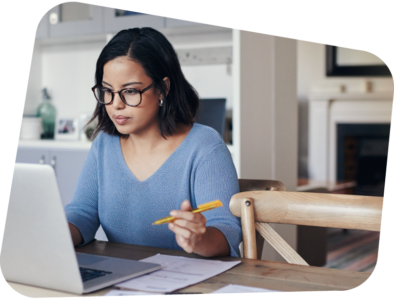 Image of a young woman completing online academic provision at a kitchen table.