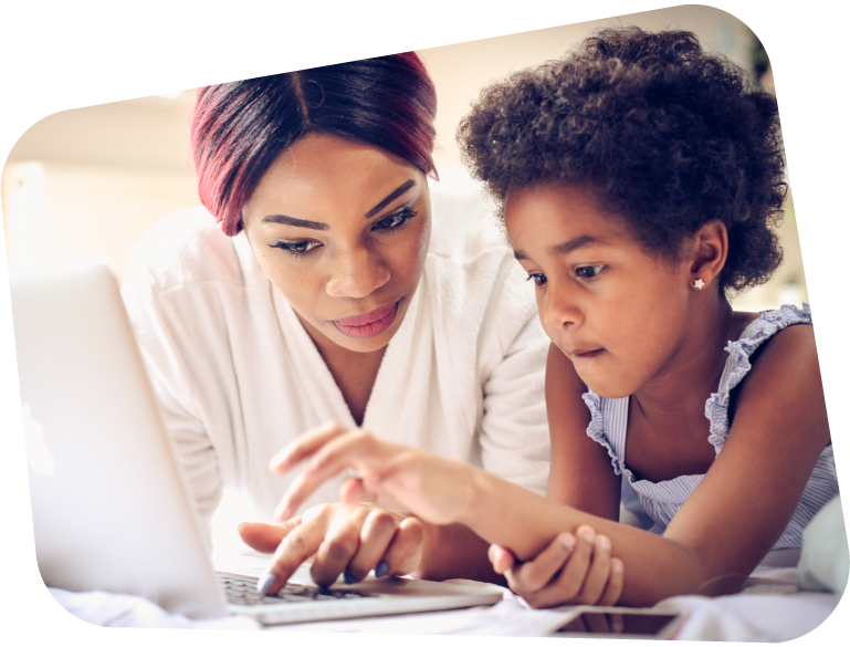 An image of a mother and daughter using a laptop together, leaning on a bed.