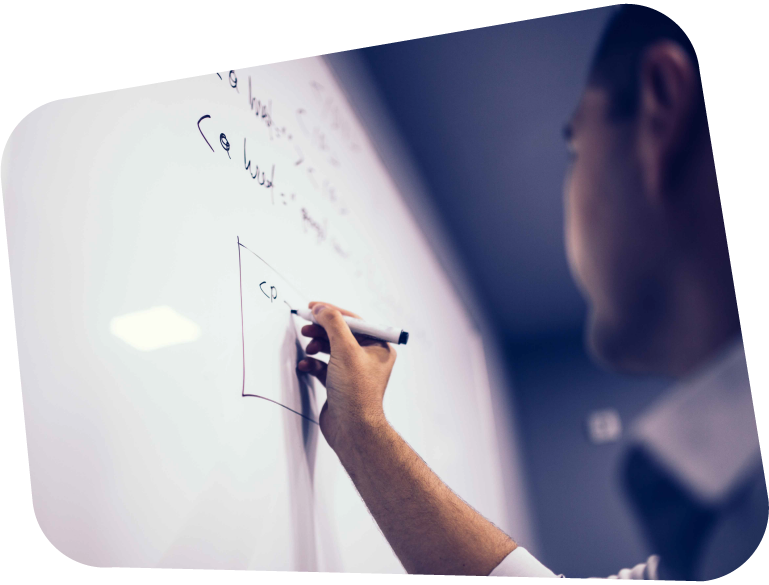 An image of a man wearing a white shirt writing an equation on a wall-mounted whiteboard.
