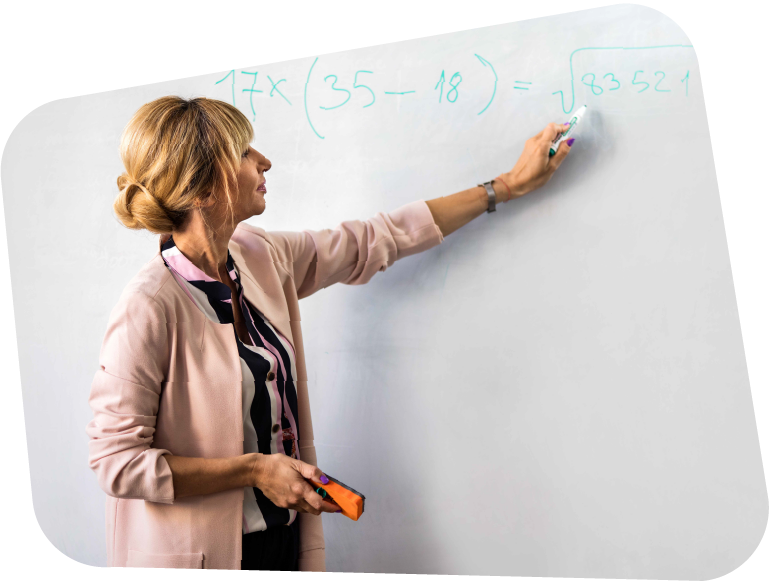A blonde haired teacher pointing to an equation on her whiteboard, wearing a pink blazer.