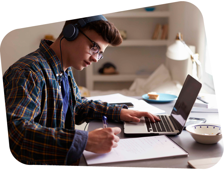 Photograph of a boy studying from home with his headphones on, a laptop on his desk and notebook and pen in hand.