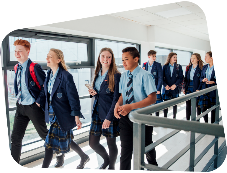 Key Stage 3 students walk down a school corridor in blue uniforms, chatting together between classes.