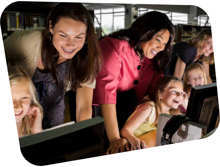 An image of three young girls on computers, each with their mothers behind them, laughing at something on their screens.