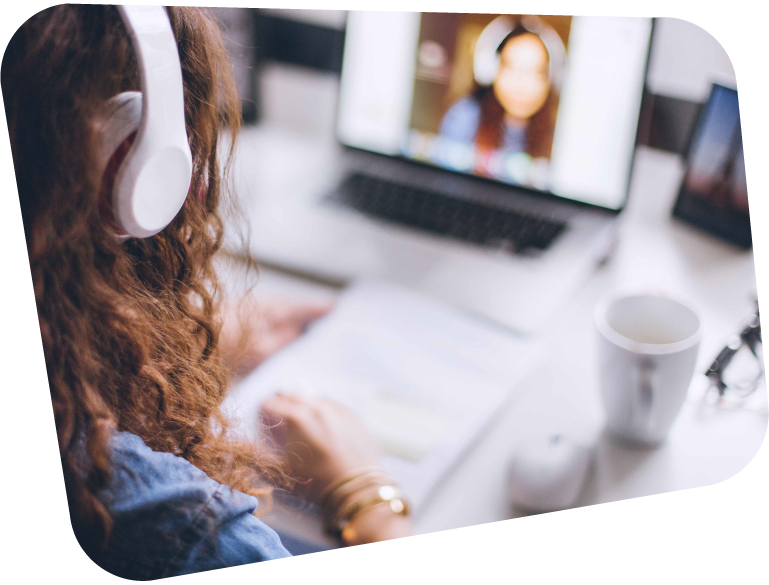 An image of a Sixth Form student wearing white headphones, in a video call from home with her teacher on her laptop.