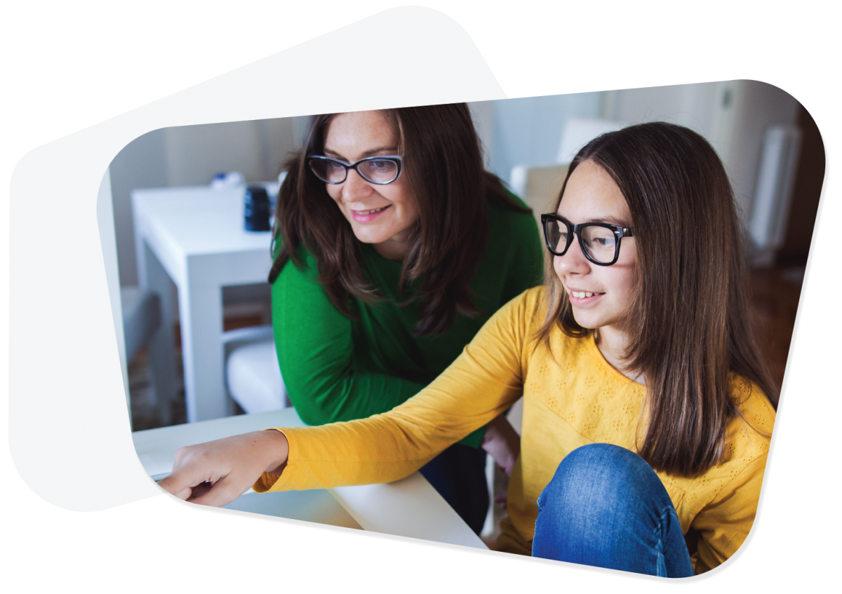 Girl in yellow jumper and her mother using a computer together.