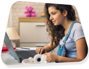 A young girl wearing denim dungarees sitting at her desk to use her laptop.